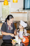 Moderundervisningdotter till att kamma hem vetemjöl Arkivfoton