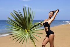 Modeschönheit im Bikini mit Palmenniederlassung Stockfotografie