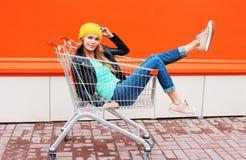 Modeschönheit im Laufkatzenwarenkorb, der schwarzen Jackenhut über bunter Orange trägt Stockfoto