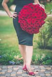 Modeschönheit trägt schwarzes Kleid hält großen Blumenstrauß von 101 roten Rosen Stockbild