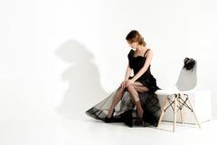 Modeschuß der eleganten traurigen Frau im schwarzen Kleid und im Schleier sitzt auf Stuhl und der Aufwartung auf weißen Hintergru Lizenzfreie Stockfotos