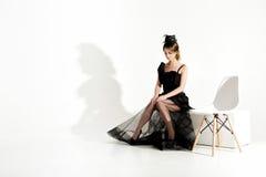 Modeschuß der eleganten traurigen Frau im schwarzen Kleid und im Schleier sitzt auf Stuhl und der Aufwartung auf weißen Hintergru Stockfotos