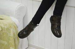 Modeshopparen lägger benen på ryggen sammanträde på en soffa hemma royaltyfria bilder