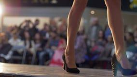 Modeshowen modellben går till podiet i hög-heeled skor i kort klänning på bakgrund av ljus och åhörare arkivfilmer