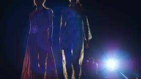 Modeshowen, modellpodiet med långa ben i skor med höga häl och aftonklänningen går på landningsbana stock video