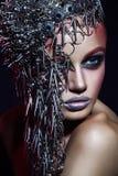 Modeskönhetmodell med röd makeup för metallisk headwear och för skinande silver och blåa röda ögonbryn för ögon och på svart bakg royaltyfria bilder