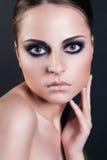 Modeskönhetståenden av den attraktiva unga kvinnan med smokeyögon utgör arkivfoto