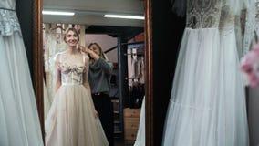 Modeskräddaren hjälper bruden väljer bröllopsklänningen Montering för bröllopkappa fashion looken lager videofilmer
