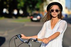 Modestående av den härliga flickan med cykeln arkivfoton