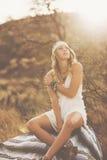 Modestående av den härliga unga kvinnan Backlit på solnedgången Royaltyfria Bilder