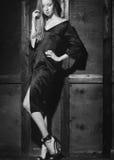 Modestående av den härliga unga kvinnan i sexig svart klänning nära med den wood väggen Elegant mörk aftonblick Fotografering för Bildbyråer