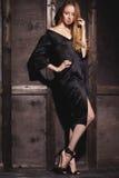 Modestående av den härliga unga kvinnan i sexig svart klänning nära med den wood väggen Elegant mörk aftonblick Royaltyfria Bilder