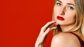 Modestående av den sexuella blonda kvinnan med provokativa glansiga röda kanter över röd bakgrund arkivfoto