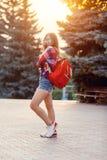 Modestående av den unga nätta hipsterkvinnan som är utomhus- med långt hår och den röda ryggsäcken i den soliga sommargatan _ royaltyfria foton