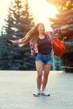 Modestående av den unga nätta hipsterkvinnan som är utomhus- med långt hår och den röda ryggsäcken i den soliga sommargatan _ arkivbilder