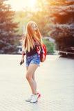 Modestående av den unga nätta hipsterkvinnan som är utomhus- med långt hår och den röda ryggsäcken i den soliga sommargatan _ royaltyfri foto