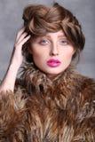 Modeståendeflickas framsida med rosa kanter och brunt hår Royaltyfri Foto