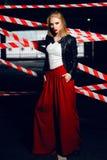 Modeståenden av den sexiga blonda flickan med röda kanter som bär en vaggasvart, utformar att posera på bakgrunden av varningsban Royaltyfri Fotografi