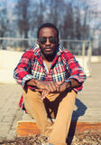 Modeståenden av den stilfulla unga afrikanska mannen lyssnar till musik Arkivfoto