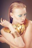 Modeståenden av glamourmodellflickan med blått och guld- gör royaltyfria bilder
