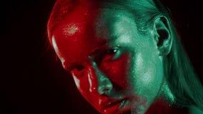 Modeståenden av kvinnans framsida blänker in och under neonljus i 80-talstil, den videopd ståenden med grönt och rött blandat arkivfilmer