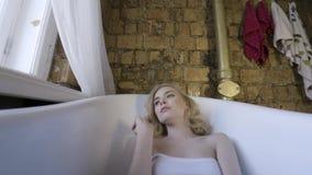 Modest?enden av en h?rlig flicka som b?r den eleganta bodysuiten, ligger i ett tomt bad och ser en kamera kvinnlig stock video