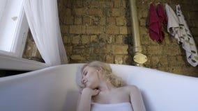 Modest?enden av en h?rlig flicka som b?r den eleganta bodysuiten, ligger i ett tomt bad och ser en kamera kvinnlig arkivfilmer
