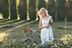 Modest girl in the garden. Modest girl walking in the park with the bike Royalty Free Stock Images