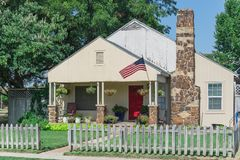 Modest home proudly displaying American flag and hanging flower royalty free stock images