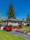 Modest residential house with car parked on asphalt driveway. Family house with blossoming flowers on the front yard royalty free stock images