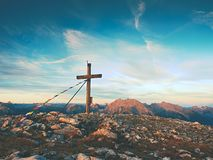 Modest wooden cross raised on rocky Alpine mountain summit . Sharp rocky peak. Gentle clouds  in blue sky. Modest wooden cross  with Buddhist praying flags Royalty Free Stock Photos