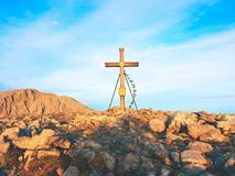 Modest wooden cross raised on rocky Alpine mountain summit . Sharp rocky peak. Gentle clouds  in blue sky. Modest wooden cross  with Buddhist praying flags Stock Image
