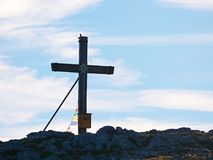 Modest wooden cross raised on rocky Alpine mountain summit . Sharp rocky peak. Gentle clouds  in blue sky. Modest wooden cross  with Buddhist praying flags Royalty Free Stock Photo