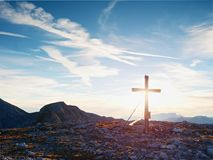 Modest wooden cross raised on rocky Alpine mountain summit . Sharp rocky peak. Gentle clouds  in blue sky. Modest wooden cross  with Buddhist praying flags Royalty Free Stock Image