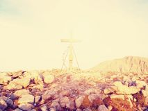 Modest wooden cross raised on rocky Alpine mountain summit . Sharp rocky peak. Gentle clouds  in blue sky. Stock Photos