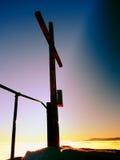 Modest wooden cross on rocky summit. Memory of victims. Modest wooden cross raised  on rocky mountain summit . Sharp snowy peak. Daybreak Sun in sky. Wooden Stock Photo