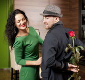 The modest young man with a rose and its girlfriend. Appointment in cafe Stock Photos