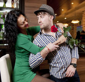 The modest young man with a rose and its girlfriend. Appointment in cafe Royalty Free Stock Photos