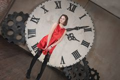 Modesty. Beautiful young girl in a red dress on the background of a large clock Stock Images