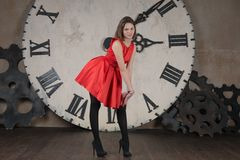 Modesty and time. Beautiful young girl in a red dress on the background of a large clock Royalty Free Stock Images