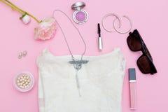 Modetillbehör, skönhetsmedel och kläder på en rosa bakgrund Royaltyfri Bild