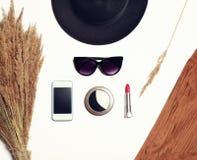 Modetillbehör, svart hatt, solglasögon, skärmsmartphone, fackspegel och röd läppstift på vit bakgrund Arkivfoto