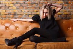 Modeung flicka på lädersoffan Fotografering för Bildbyråer
