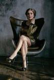 Modezaubermädchen, das im braunen Lederstuhl sitzt Lizenzfreies Stockfoto