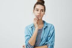 Modieus betoverend meisje die met broodjeskapsel opzij terwijl bijtende lip en wat betreft kin die, kijken worden geconcentreerd  stock foto's