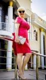 Modieus blonde in een rode kleding bij de concertzaal Stock Afbeelding