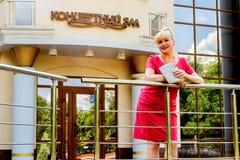 Modieus blonde in een rode kleding bij de concertzaal Stock Fotografie