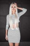 Modieus blonde jonge vrouw die in openlucht stellen Stock Afbeeldingen