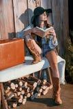 Modieus Boheems meisje die een boekzitting op een bank in a lezen royalty-vrije stock foto
