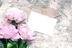 Modieus brandmerkend model om uw kunstwerken te tonen lege groetkaart of huwelijksuitnodiging met roze pioenbloemen stock foto
